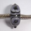 Zwart met paars-zwart-witte vlekjes en stipje in het midden